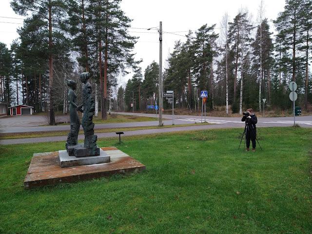 Valokuvaaja kuvaa veistosta puistoalueella, taustalla tienristeys.