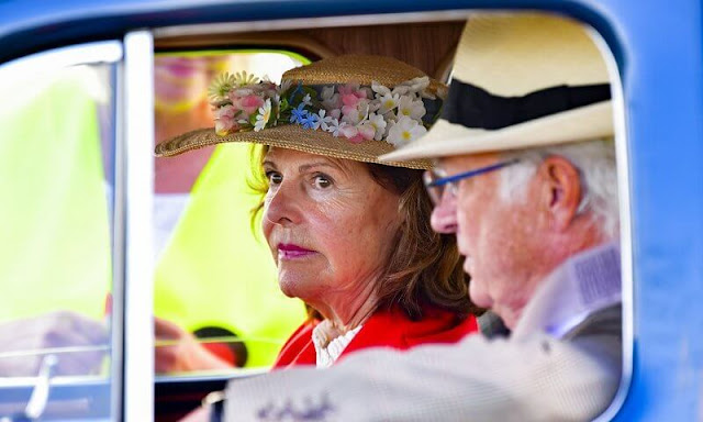 The King arrived at the event field driving his Volvo PV60 car. Queen Silvia wore a red blazer jacket double breasted with gold button
