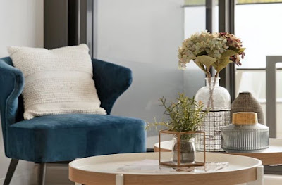Blue accent chair with white throw pillow.