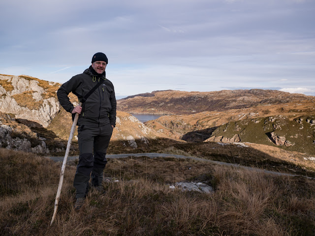 Bob Marshall standing roughly half way along Calum's Road where the road drops steeply down towards a small inlet at the head of Loch Arnish