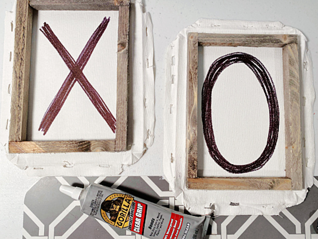 stained wooden frames on top of the x and O with glue