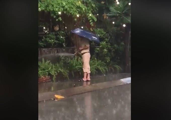 Người đàn ông đứng tưới cây giữa trời mưa