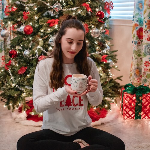 Madalyn sitting on floor in front of Christmas tree wearing Candace Cameron Bure Joy Love Peace Long Sleeve T-Shirt while looking down at the Names Of Jesus Ceramic Mug in her hand.