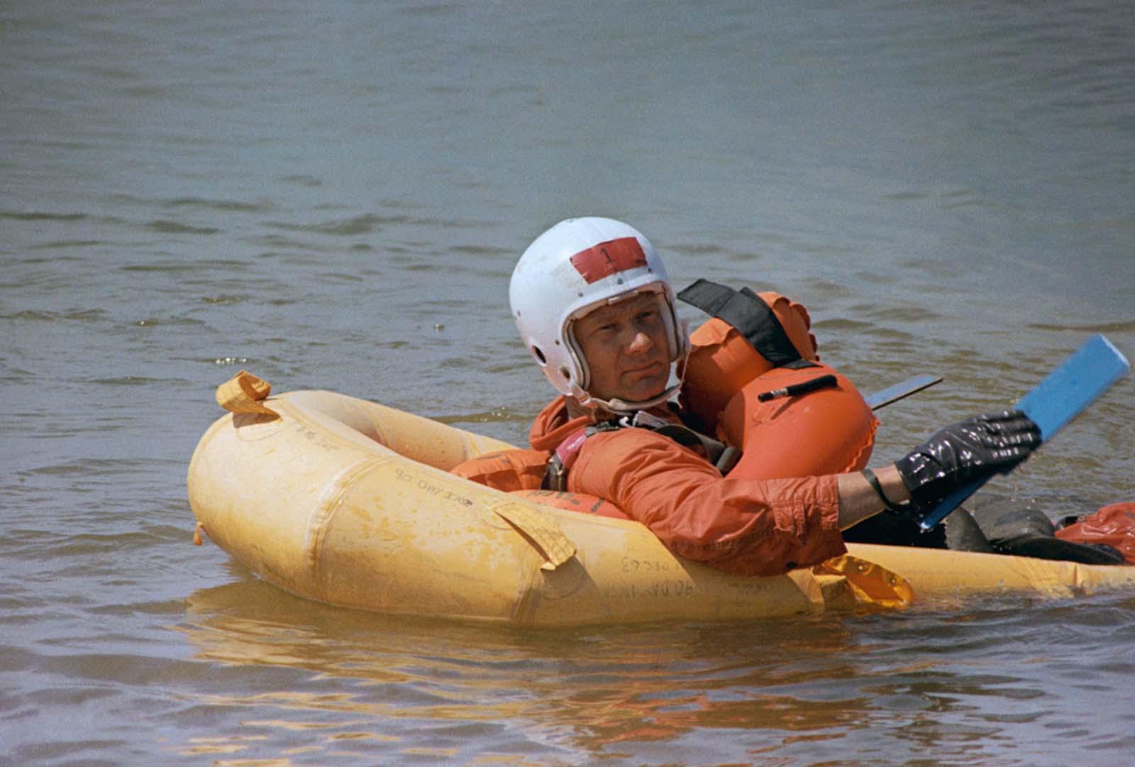 O astronauta Buzz Aldrin rema à costa do Lago Texoma durante o treinamento na Escola de Apoio à Vida do Comando de Defesa Aérea da Força Aérea dos EUA na Base Aérea de Perrin em Sherman, Texas. Ele senta em um bote salva-vidas de um homem só. Ele foi jogado na água depois de fazer uma subida de parasail a cerca de 400 pés acima do lago.