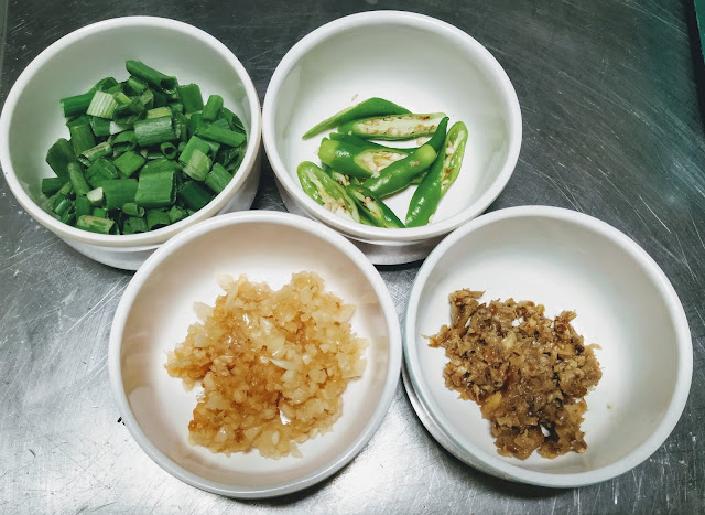 Chopped Garlic Ginger spring onions and slit green chili for chilli paneer recipe