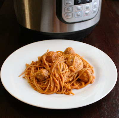 serving of creamy spaghetti and meatballs on plate