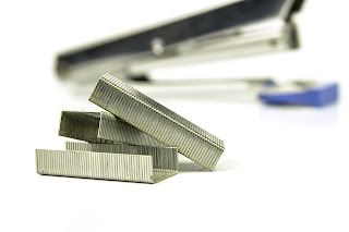 This is a photograph of staples and a stapler in the background.