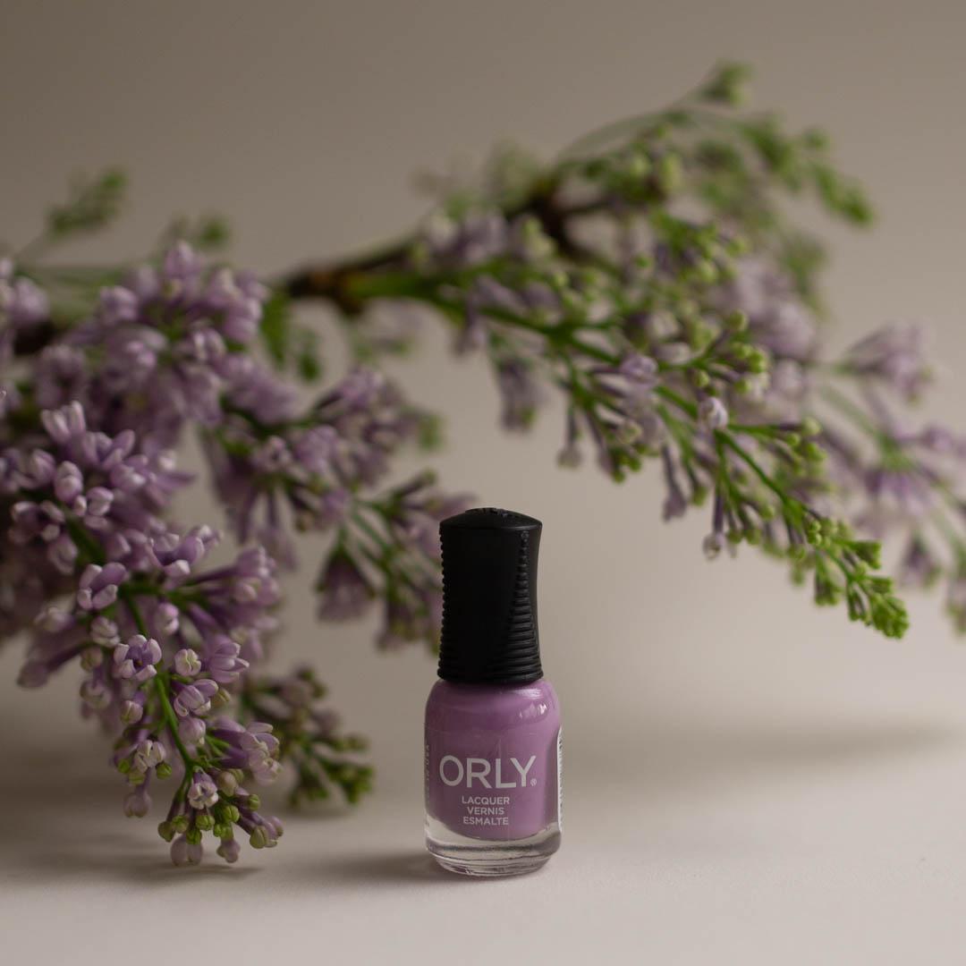 Vaalean alustan päällä kynsilakka, ja taustalla / vieressä kynsilakan kanssa saman sävyinen, laventelin värinen kasvi.