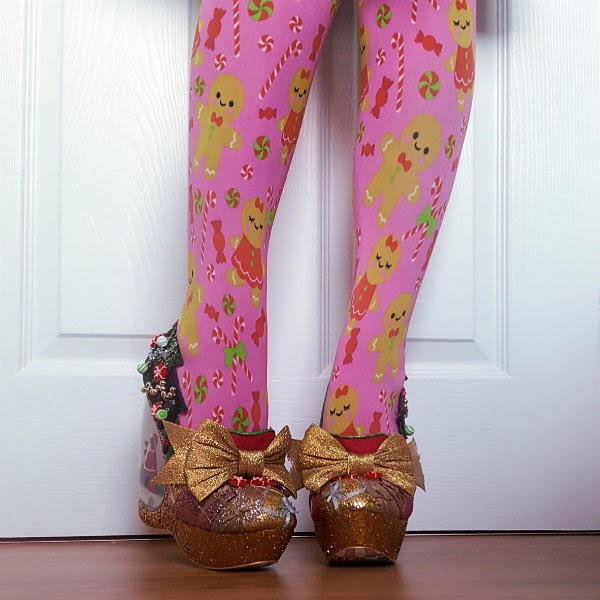tilted leg wearing festive gingerbread tights and glitter bow and christmas tree shoes