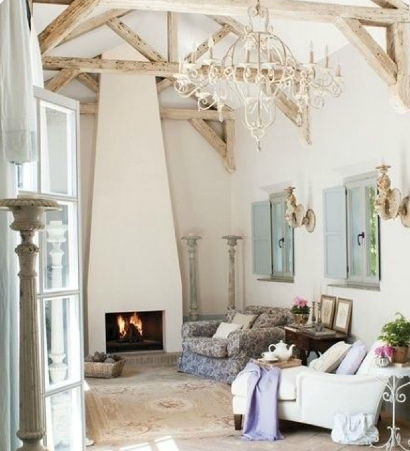 Lofty #Frenchfarmhouse living room with grand chandelier, ceiling trusses, and minimal modern fireplace