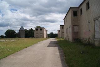 Das Bild zeigt mehrere Zweckbauten mit zugemauerten Fenstern. Im Hintergrund steht die Kirche.