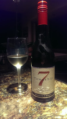 A wine glass and a bottle of Pinot Gris by Township 7 Vineyard and Winery