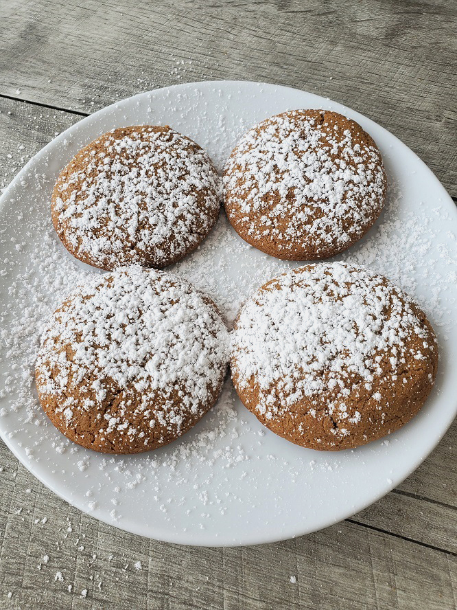 these are 4 molasses cookies on a white plate