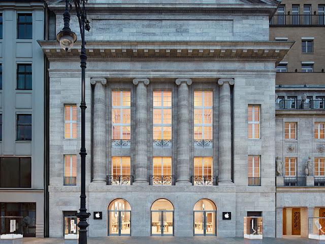 exterior edificio clásico de tienda apple con luz cálida interior, berlin