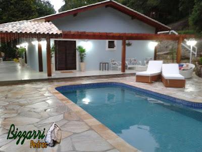 Construção de piscina em alvenaria com o revestimento de azulejo com o piso da piscina com pedra São Tomé sendo tipo cacão com a construção da residência com o pergolado de madeira.