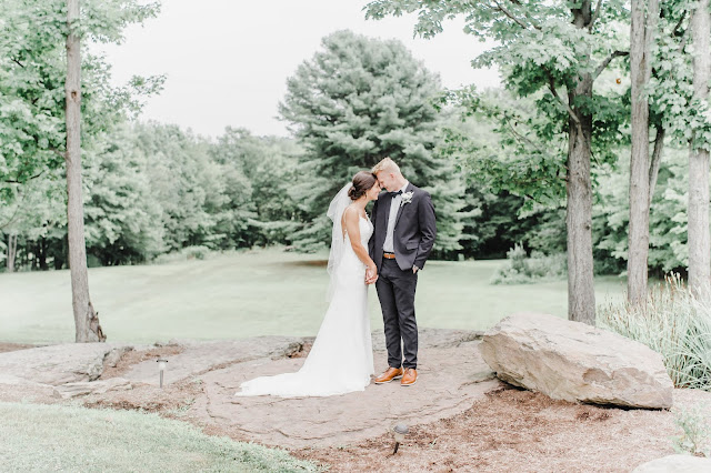 bride and groom standing on rocks