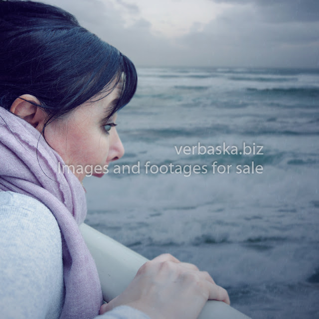 A mature woman is under the aquaphobia attack. She is feeling scared when looking at the stormy sea.