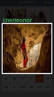 на выходе из пещеры стоит спелеолог в каске и с фонарем в руках