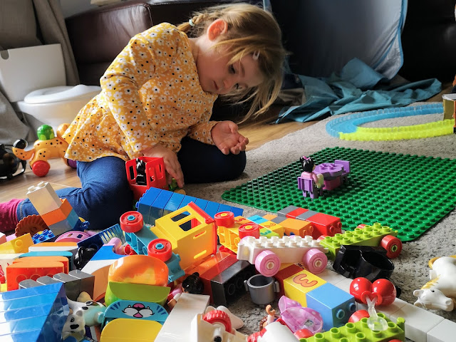 Image of a young girl in a yellow floral top and jeans. She is sat on the floor and is leaning forward playing with Duplo. Strewn across the floor are several sets of Duplo including a Duplo Number Train, Duplo My First Animals, Duplo Farm Set and The Duplo Disney Minnie and Mickey Train Set. The girl is putting the blocks together and building onto a Duplo Base Plate.