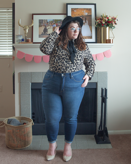 An outfit consisting of a black wide brim fedora, a brown animal print button down blouse with a black ribbon tied in a bow under the collar tucked into blue high waist jeans and nude heels.