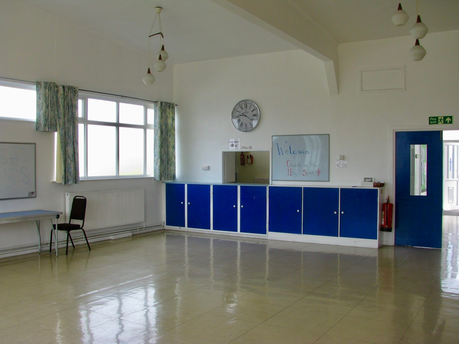 Showing off further space including storage and white board. Windowed space to two walls letting in sun light. to left of image  is a windowed  unit to the canteen with storage below in blue doors.