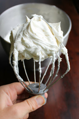 beater from stand mixer inverted with a pile of fluffy white ermine frosting on top