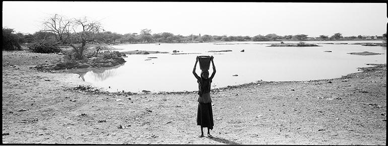 Photo d'une jeune fille au Sahel portant un seau sur la tête prise par Philippe de Poulpiquet