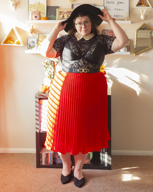 An outfit consisting of a wide brim black hat, a short sleeve black lace dress with cream color and cream cuffs with a black harness style bralette over, tucked into a red pleated midi skirt and black pointed toe slingback flats.
