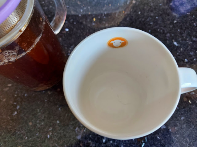 Photo showing the clean inside of a white mug.  To the left is a pot of tea