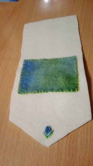 Eerste opzet van een vilten tasje, wit met een blauwgroen vlak en een geborduurd roosje.