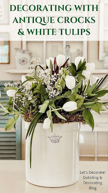 Creating a festive floral arrangement for Spring and Saint Patrick's Day with antique crocks and white tulips.