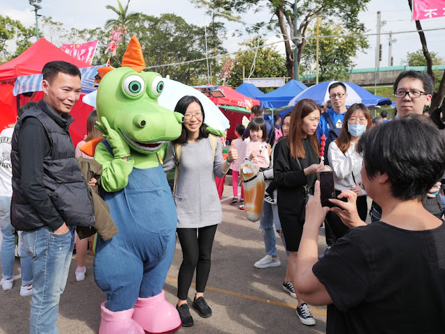 people posing with Ah Tak at the Fa Hui Lunar New Year Fair