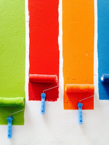 Four paint rollers painting different colors of paint on white wall