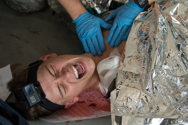 A man who appears to be in pain. There are gloved hands on the man's shoulder.