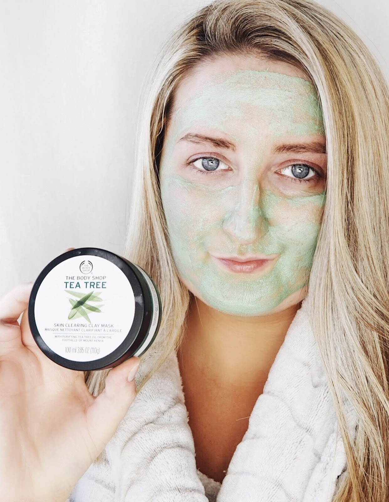 Blonde girl holding and wearing (having applied) The Body Shop Tea Tree Skin Clearing Clay Face Mask against a white background in a bathroom setting