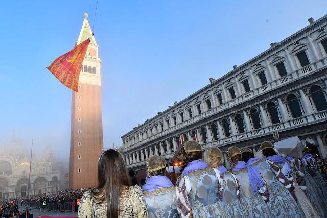 Nejhezčí dívky Benátského karnevalu sledujíc stoupající benátskou vlajku