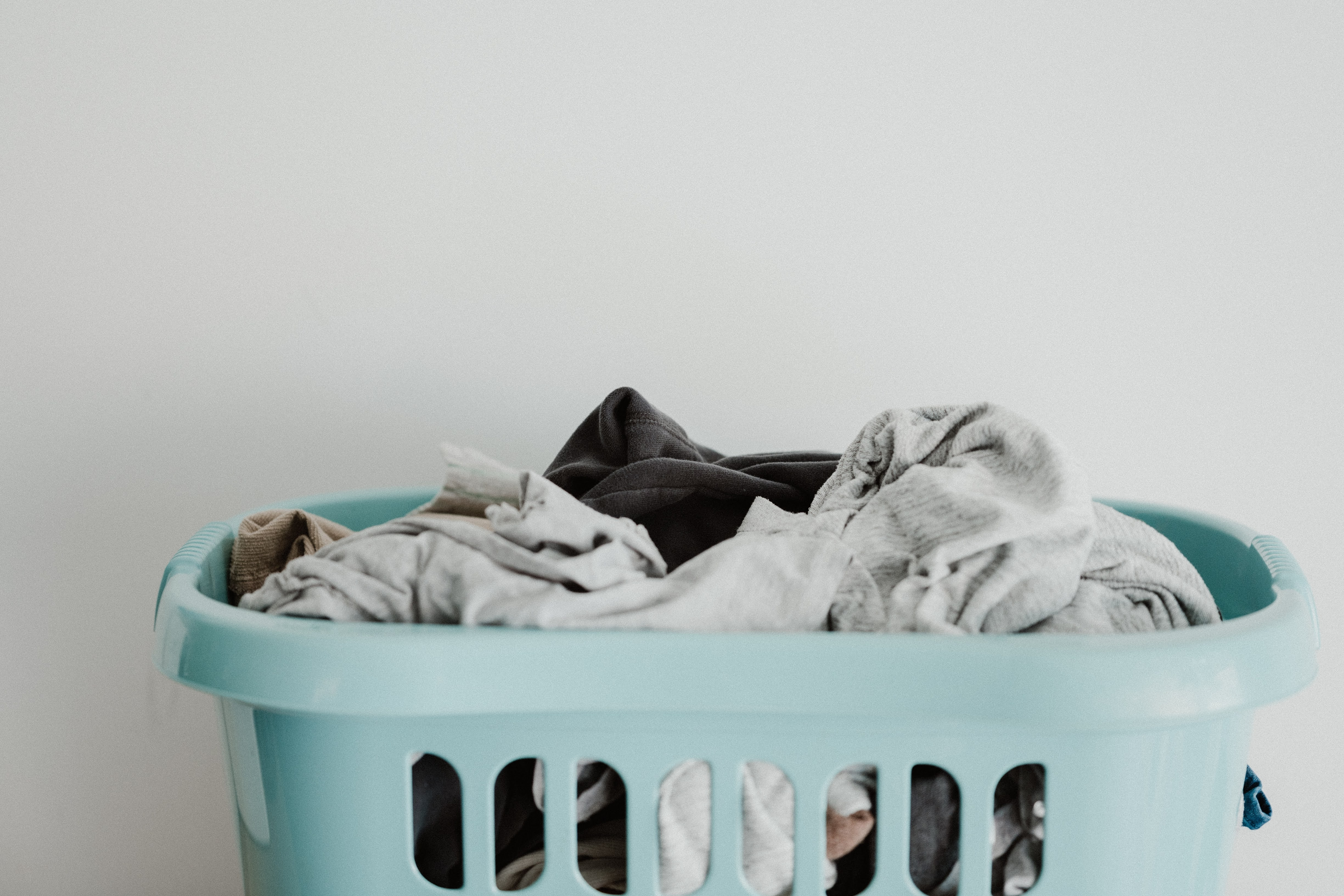 White Textile on Blue Plastic Laundry Basket | Photo by Annie Spratt via Unsplash
