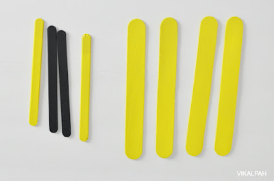 yellow and black craft sticks on a white background