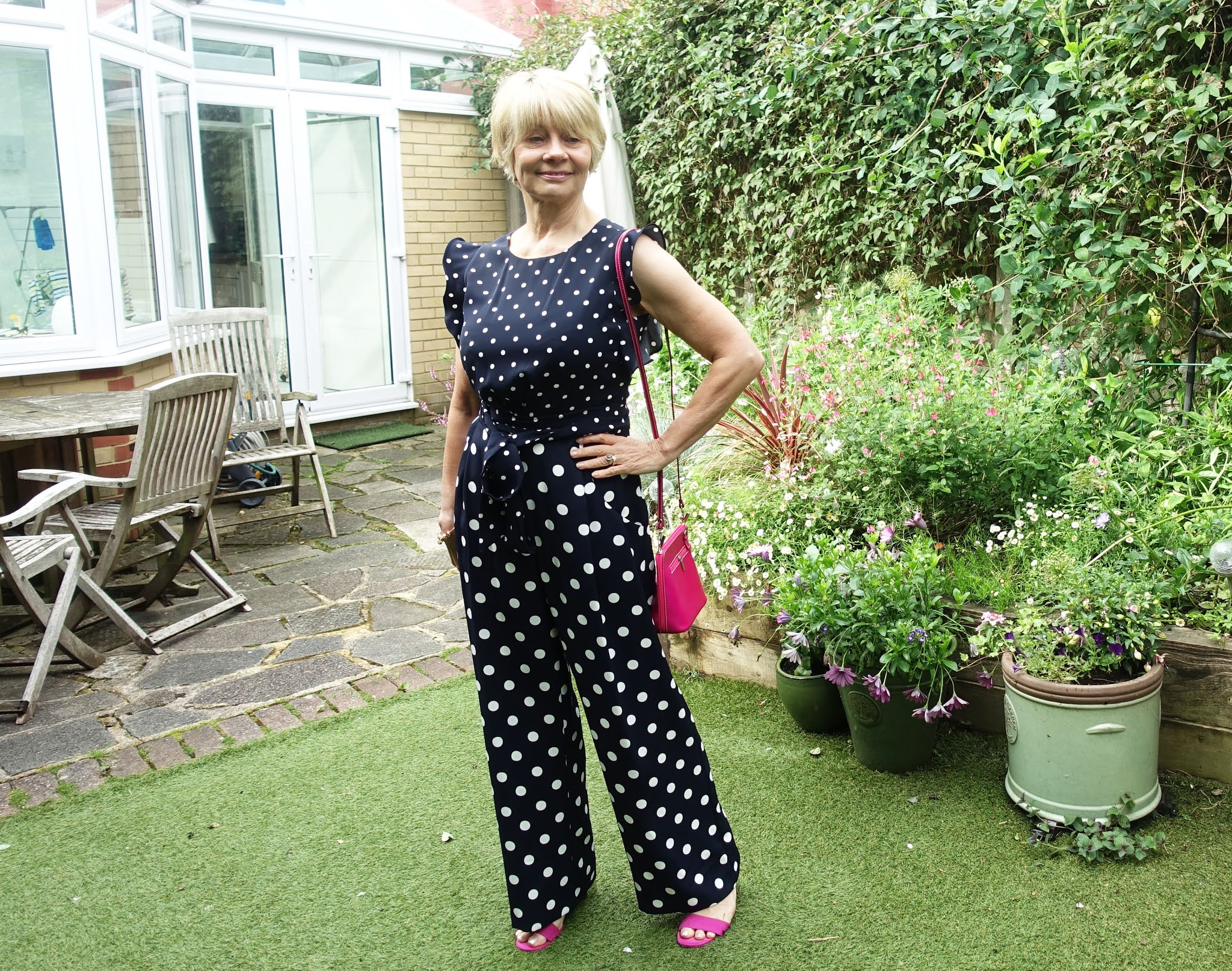 Over 50s blogger Gail Hanlon in navy and white polka dot jumpsuit and bright pink accessories