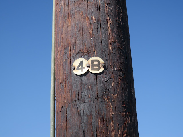 Wooden pole with 4b labelled on it.