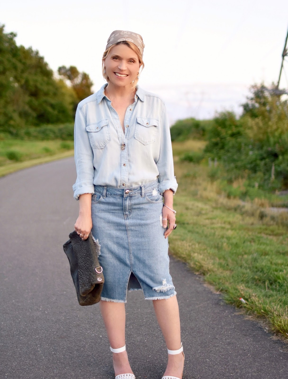 styling a distressed denim pencil skirt with a chambray shirt, studded ankle-strap sandals, and a paisley headscarf