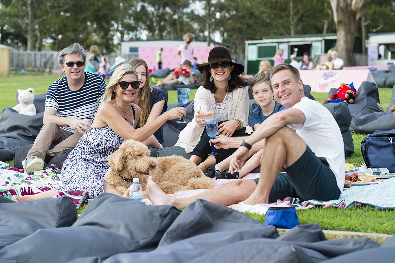 Family with their Oodle dog sits on a picnic rug at Moonlight Cinema in Centennial Park