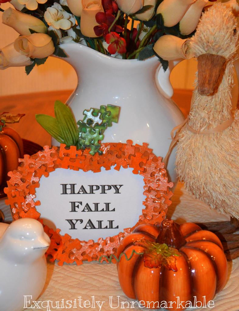 Puzzle Piece Pumpkin frame sign surrounded by bird statues and glass pumpkins