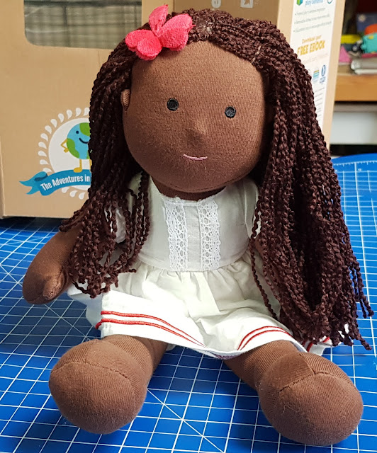One Dear World Hearty Hope doll sitting on table unsupported with white dress, brown skin and long curly hair.