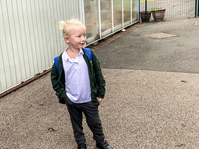 First day of nursery and in school uniform: grey trousers, white top, green cardigan