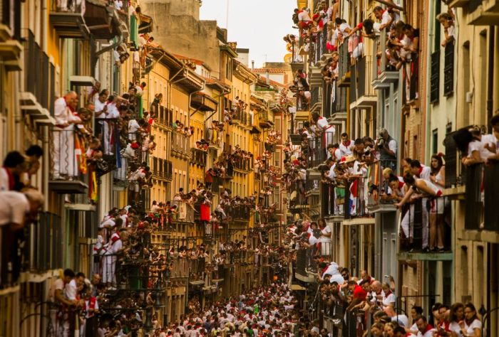 People watching the Running of the Bulls in Pamplona, Spain. Running of the Bull is part of San Fermin, and people come to Pamplona from all over the world to celebrate this festival every year. This kind of scene in the narrow streets will appear once a day in the eight-day event.