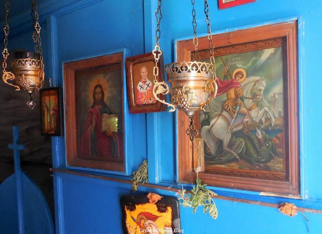 wnętrze greckiej cerkwi, wiszące kantili, ikony świętych zawieszone na niebieskiej ścianie