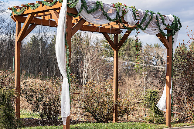 Ceremony detail shot of wood arch with white veil and greenery Magnolia Farm Asheville Wedding Photography captured by Houghton Photography