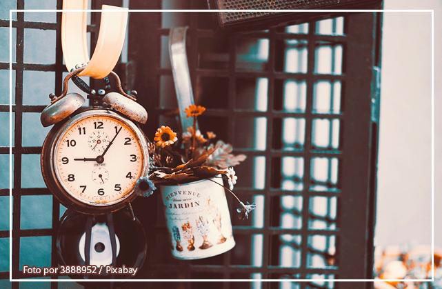imagem mostra um relógio e um vaso de flores antigos pendurado em uma alça de metal, em frente a um portão
