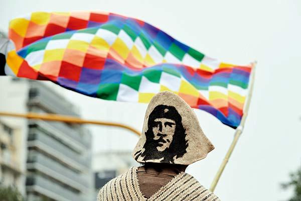 Una persona de espaldas vestida con poncho lleva un sombrero con la imagen del Che Guevara y porta la bandera wiphala
